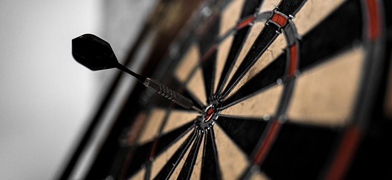 Image of a dart hitting the bullseye on a dartboard. Original Photo by Anastase Maragos on Unsplash.